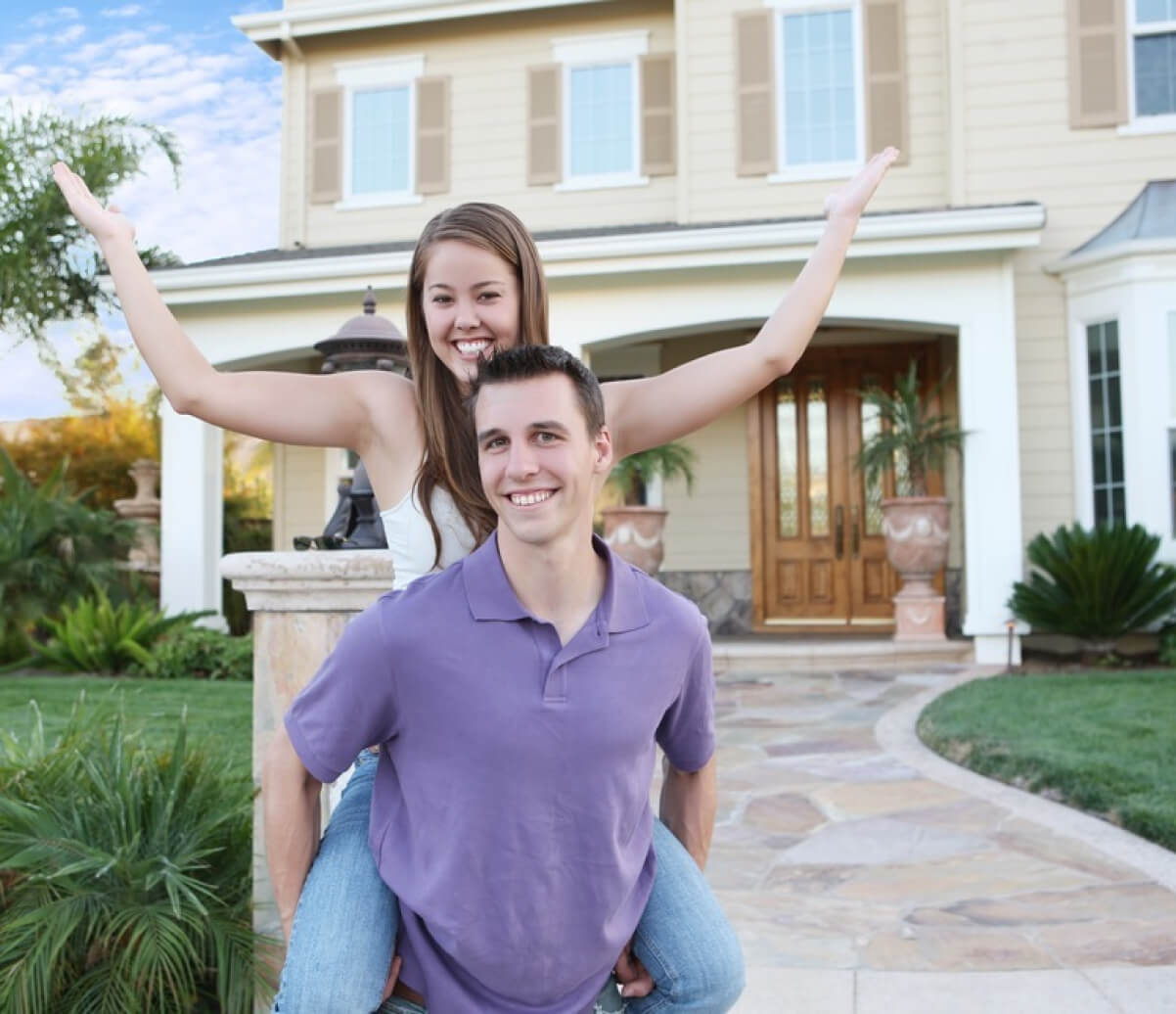 Happy couple in front of a house